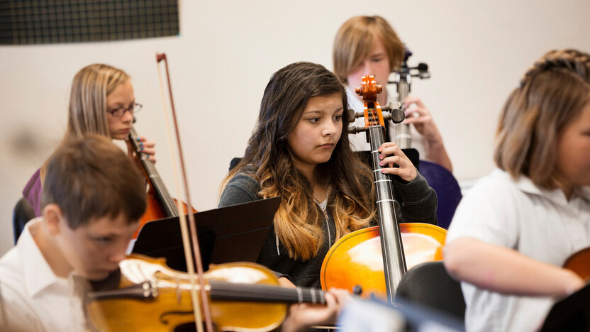Children indoor Students playing string instruments in music class. Indoor, concentration, acoustics.