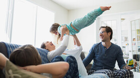 People indoor living room Playful mother lifting daughter overhead on sofa
