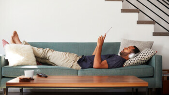 Man Lying On Sofa At Home Wearing Headphones; Shutterstock ID 1125901364;  Used for Sustainability Report 2018.