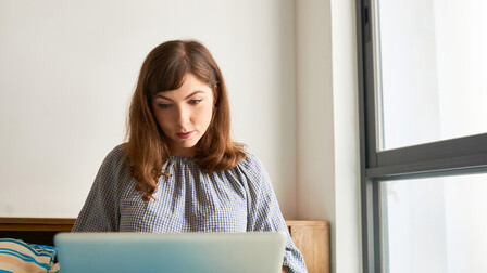 Businesswoman reading documents on screen of her laptop in office; Shutterstock ID 1325019239; Used for Sustainability Report 2018. 