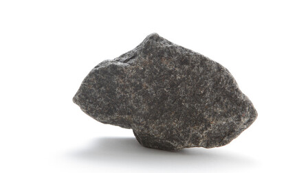 Basalt rock on white background. iStock-184656596; Used for Sustainability Report 2018.   Geology; Gray; Material; Mineral; Rock; Single Rock; Stone; White Background; Basalt; Close-up; Cut Out;