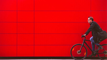 WILL BE DELETED SOON (safety issues) Man riding bicycle in front for red wall iStock-627884444; Used for cover of Sustainability Report 2018.   Vibrant Color; Real People; Travel; Male; Traveling; Businessman; Men; City Life; Commuter; Healthy Lifestyle; Caucasian Ethnicity; Business Travel; One Person; Vitality; On The Move; Red; Modern; Urban Scene; Outdoors; Horizontal; Cycling; Street; Bicycle;  Riding; Bike