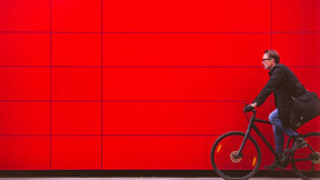 Man riding bicycle in front for red wall iStock-627884444; Used for cover of Sustainability Report 2018.   Vibrant Color; Real People; Travel; Male; Traveling; Businessman; Men; City Life; Commuter; Healthy Lifestyle; Caucasian Ethnicity; Business Travel; One Person; Vitality; On The Move; Red; Modern; Urban Scene; Outdoors; Horizontal; Cycling; Street; Bicycle;  Riding; Bike