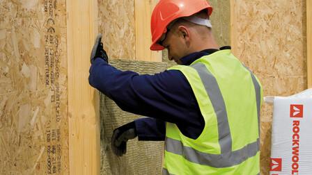 Builder installing ROCKWOOL insulation - Timber frame construction