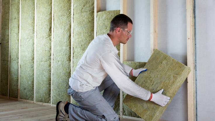 Man installing insulation, Self-builder, Renovation, Timber Frame Wall