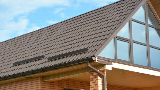Building Modern House Construction with metal roof, rain gutter system and roof protection from snow, snow bar (Snow guard). Roof Snow Guards: Building Materials & Supplies. Attic skylight window.